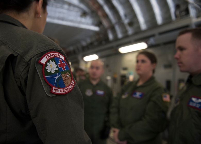 A 183rd Air Evacuation Squadron patch sits on an Airman's flight suit. in front of three Airmen.