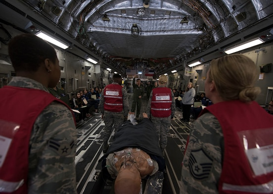 Air Force Airmen lift a CPR mannequin in a C-17 Globemaster III assigned to Thompson Field Air National Guard Base, Mississippi for Operation Foremost Endeavor at Nellis Air Force Base, Nev. Feb. 20, 2019. The goal of the exercise was to give officials, observers, media personnel and players from participating organizations information they need to observe or participate in a National Disaster Medical System hospital evacuation, aeromedical evacuation and patient reception exercise. The exercise focuses on participants' emergency response plans, policies and procedures as they pertain to a medical surge incident resulting from a disaster in the state of California. (U.S. Air Force photo by Airman 1st Class Bryan Guthrie)