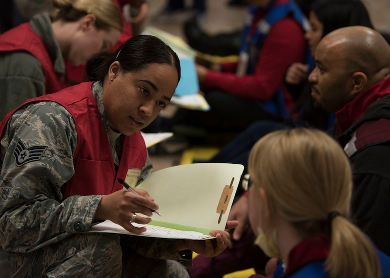 An Airman holds an open folder while speaking to a civilian.