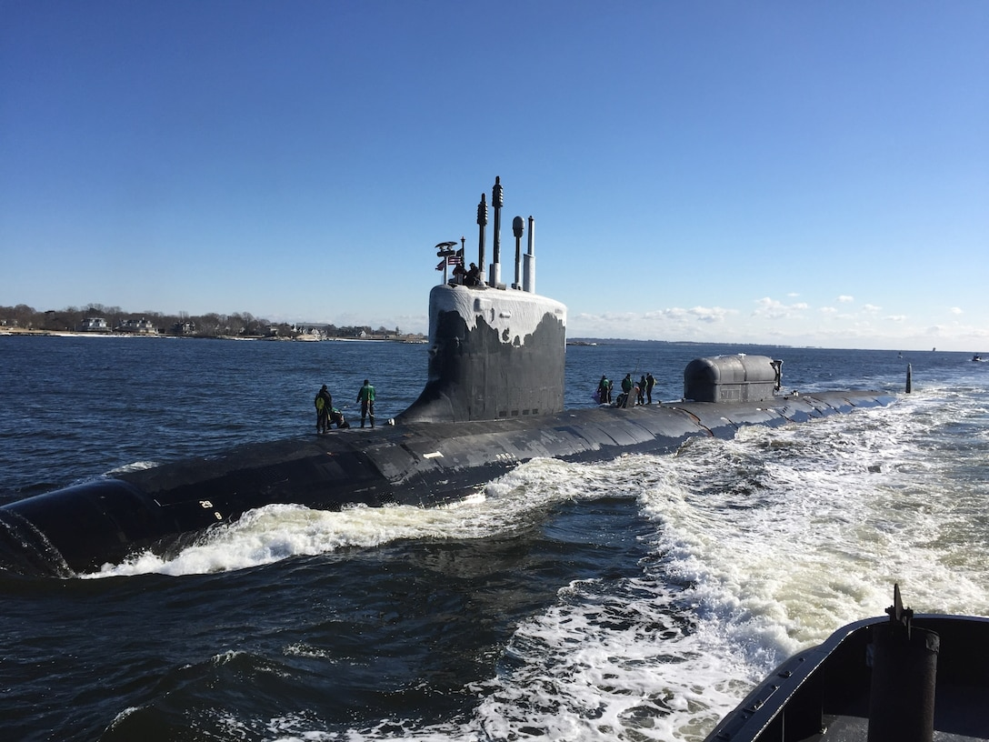 Sailors stand atop a submarine as it heads to port.