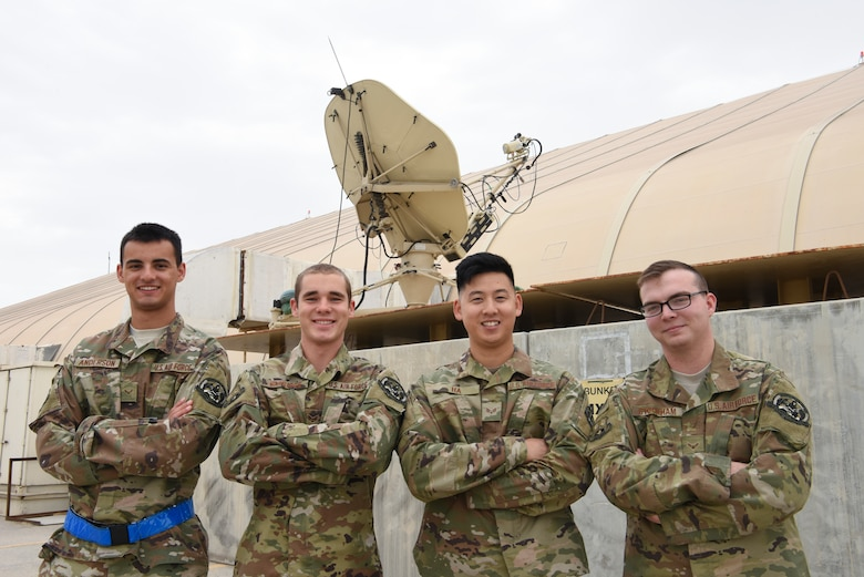 380th Expeditionary Aircraft Maintenance Squadron grounds communication technicians Airman 1st Class Trevor Anderson, Senior Airman Seth Oatridge, Airman 1st Class Michael Ha, and Airman 1st Class Brandon Stockham pose for a group photo in front of their communication satellite, Feb. 17, 2019 at Al Dhafra Air Base, United Arab Emirates.