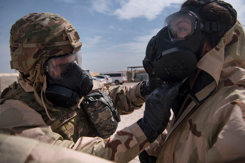 U.S. Army Pvt. Mason Hage (left), 1st Battalion, 43rd Air Defense Artillery (ADA) regiment, 11th ADA Brigade patriot fire control enhanced operator and maintainer, helps U.S. Air Force Staff Sgt. Rikki Sechrist (right), 379th Expeditionary Civil Engineer Squadron (ECES) emergency management Chemical, Biological, Radiological, Nuclear, and high yield explosives (CBRNE) specialist, adjust Mission Oriented Protective Posture (MOPP) gear during a joint decontamination exercise Feb. 22, 2019, at Al Udeid Air Base, Qatar. U.S. Air Force and Army participants from the 379th ECES and the 1-43rd ADA, shared CBRNE best practices, and tested their response proficiency during the training. The event was the conclusion of a four phase training curriculum. (U.S. Air Force photo by Tech. Sgt. Christopher Hubenthal)