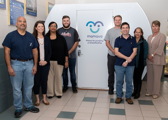 Naval Surface Warfare Center Panama City Division (NSWC PCD) and Lynxnet personnel pose for a photo in front of one of three new Mamava nursing pods. Pictured from left to right: Benji Garcia, Danielle Kinkade, Carmelita Martin, Steve Blackmon, Tyler Dennis, Jason Zimmerman, Robbie Kurth, and Mary Hulgan. The nursing pods are designed to create a comfortable nursing environment for working mothers.