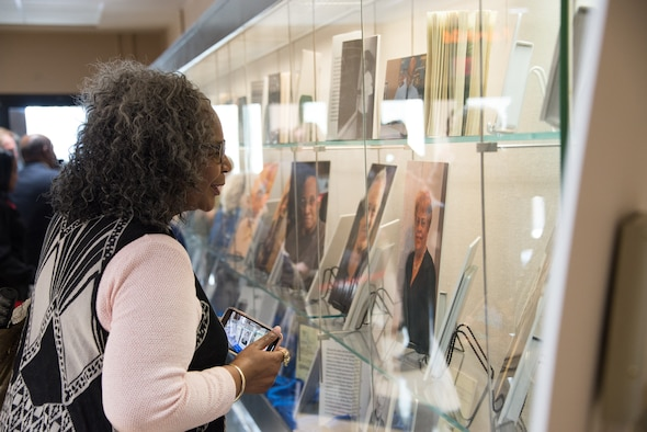 "An attendee of the ""Maxwell and the Movement"" exhibit looks over the pictures on display at the Muir S. Fairchild Research Information Center, Feb. 21, 2019, Maxwell Air Force Base, Alabama. The exhibit displayed photos and writings highlighting the successes and challenges overcome by African – Americans here at Maxwell. (U.S. Air Force photo by Senior Airman Francisco Melendez – Espinosa)"