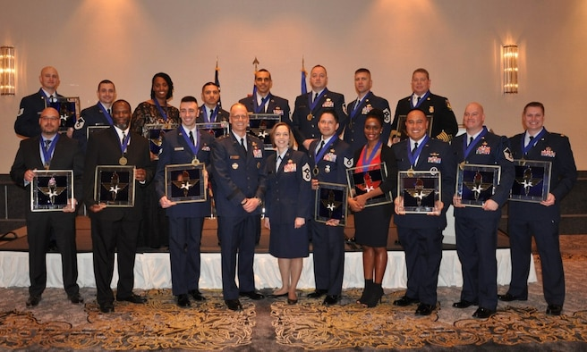 Winners of the 2018 Air Education and Training Command Outstanding Airmen of the Year awards stand with Maj. Gen. Mark Weatherington (third from left) and command chief of AETC, Chief Master Sgt. Juliet Gudgel (fourth from left) during a ceremony in Orlando, Fla., Feb. 26, 2019.  A total of 21 Airmen were recognized at the event and move on to the the Air Force-level competition. (U.S. Air Force photo by 1st Lt. Kayshel Trudell)