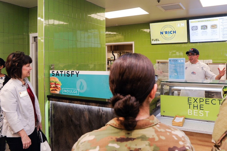 Kelly Barrett, 18th Air Force Key Spouse, left, listens to Senior Airman Christopher Maurer, 628th Force Support Squadron food service journeyman, right, Feb. 12, 2019, at the Gaylor Dining Facility at Joint Base Charleston, S.C
