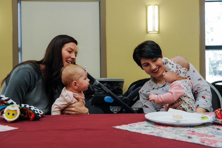 Joint Base Charleston spouses Jordan Ashley, left, and Hannah Wilson, right, let their five-month-old daughters, Nora and Maeve, interact with each other Feb. 13, 2019, during a Key Spouse luncheon at the base chapel on Joint Base Charleston, S.C.