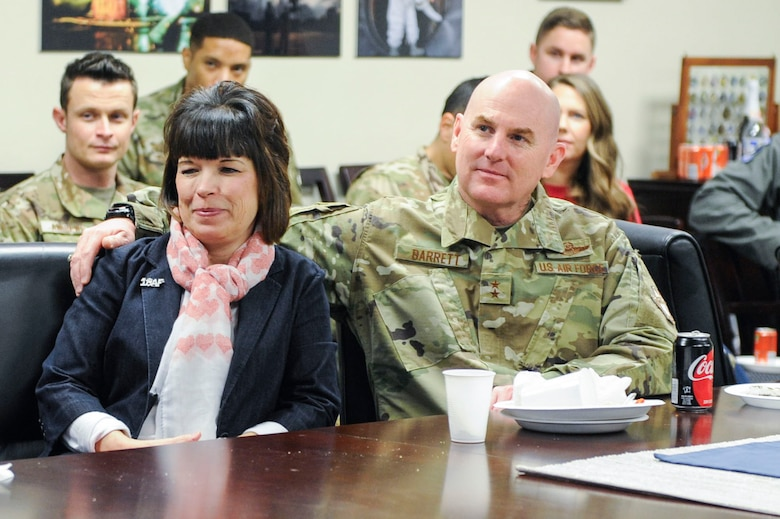 """Major General Sam Barrett, 18th Air Force commander, holds his wife, Kelly, while Staff Sgt. Trevor Childs, assigned to Joint Base Charleston's protocol office, plays """"Can't Help Falling in Love"""" by Elvis Presley for the family members present during a luncheon Feb. 14, 2019, in the 437th Airlift Wing conference room on Joint Base Charleston, S.C."""