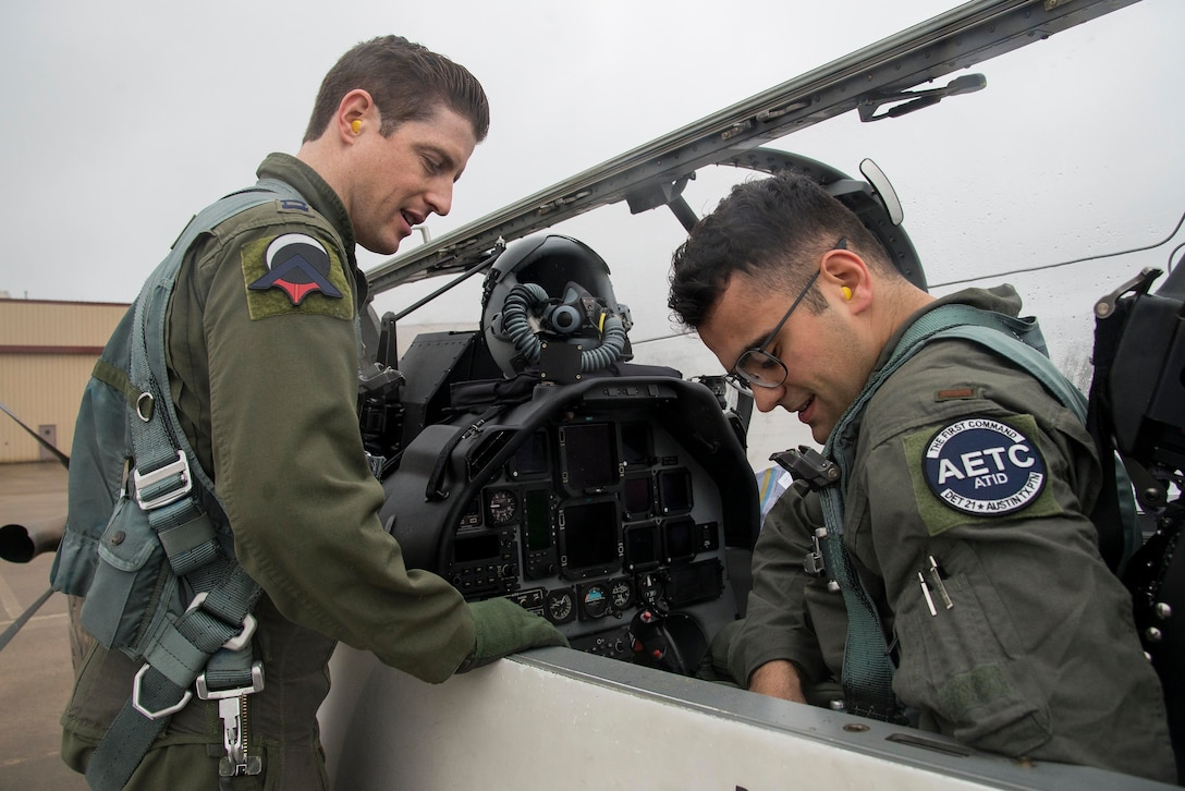 Capt. Ray Stone (right), Pilot Training Next instructor pilot, ensures Second Lt. Naji Bseiso, PTN student, is properly strapped into the T-6 Texan aircraft prior to a training mission at Austin-Bergstrom International Airport in Austin, Texas, Feb. 5, 2019. The current PTN class, which began Jan. 17, 2019, is comprised of 26 students, including 16 active duty officer students (six of whom are participating in a remotely-piloted aircraft only track), two Air National Guard officers, two U.S. Navy officers, one Royal Air Force officer, and five enlisted Airmen. (U.S. Air Force photo by Sean M. Worrell)