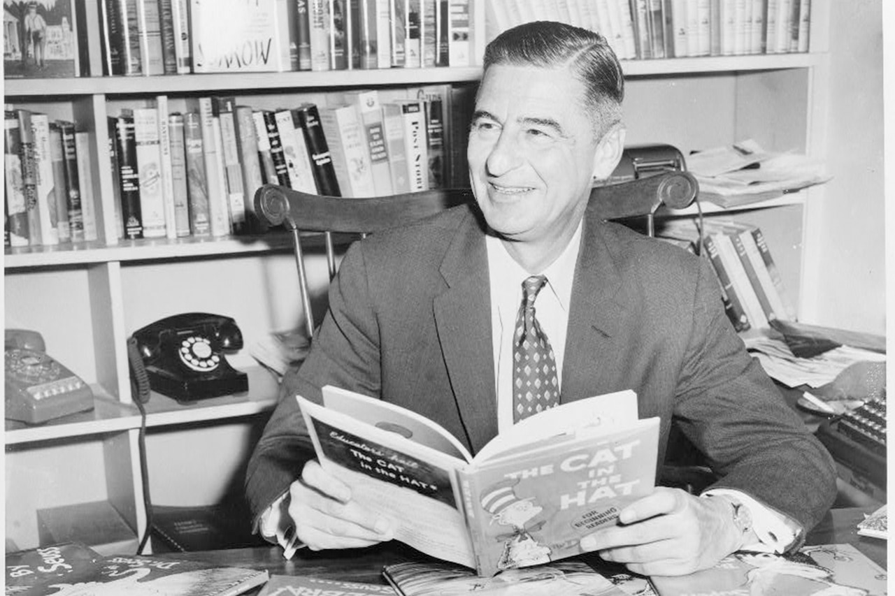 A man seated at desk covered with books holds a book and smiles.