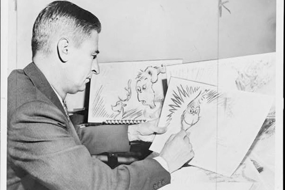 A man sits at a desk drawing cartoons on paper.