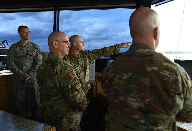 Chief Master Sgt. Chris Simpson, 18th Air Force command chief master sergeant, and Maj. Gen. Sam C. Barrett, 18th Air Force commander, are briefed by Senior Master Sgt. Kristopher R. Russ,  627th security Forces Squadron operations superintendent, inside the air traffic control tower at Joint Base Lewis-McChord, Wash., Feb 20, 2019.