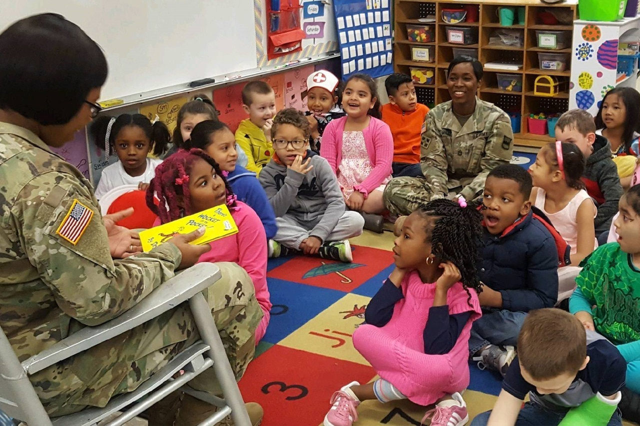 A service member reads to children.
