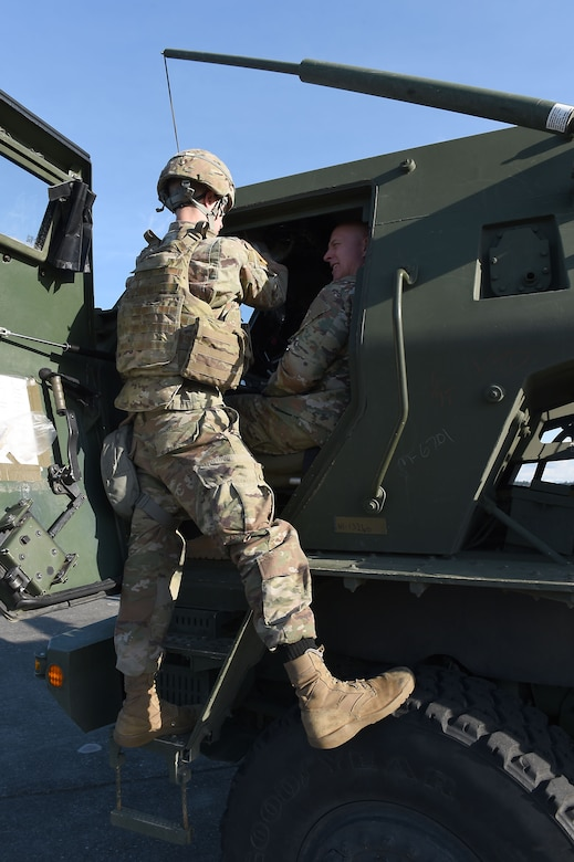 Chief Master Sgt. Chris Simpson, right, 18th Air Force command chief master sergeant, sits as a soldier from the 17th Field Artillery Brigade highlights the unique capabilities of the high mobility artillery rocket systems (HIMARS) on Joint Base Lewis-McChord, Wash., Feb. 21, 2019.