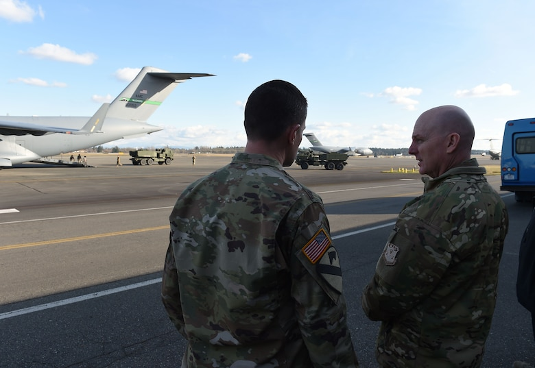 Maj. Gen. Sam Barrett, 18th Air Force commander, right, observes as U.S. Army high mobility artillery rocket systems (HIMARS) offload from a McChord C-17 Globemaster III on Joint Base Lewis-McChord, Wash., Feb. 21, 2019.