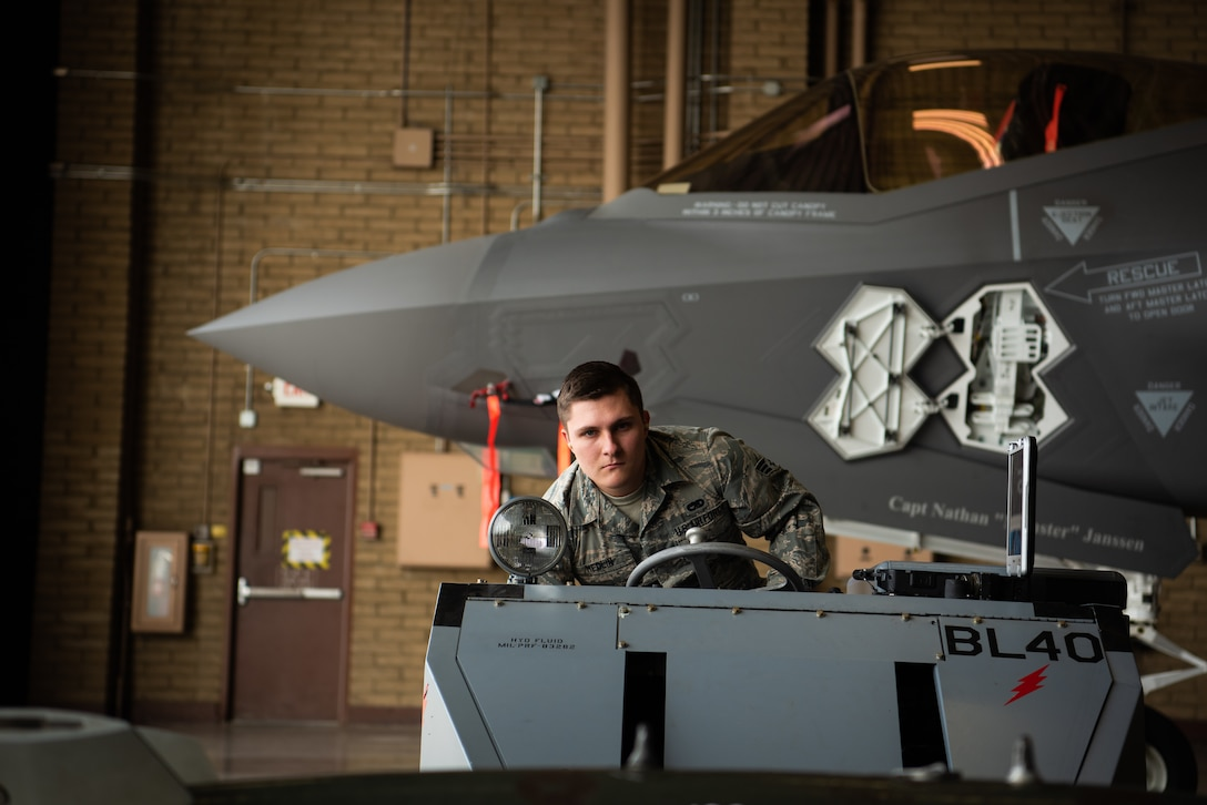 Senior Airman Hunter Medlin, 56th Component Maintenance Squadron load crew member, maneuvers a jammer underneath a dummy missile, Feb. 13, 2019 at Luke Air Force Base, Ariz. Medlin was part a three-man team receiving their certification on loading external munitions on an F-35A Lightning II. (U.S. Air Force photo by Airman 1st Class Aspen Reid)