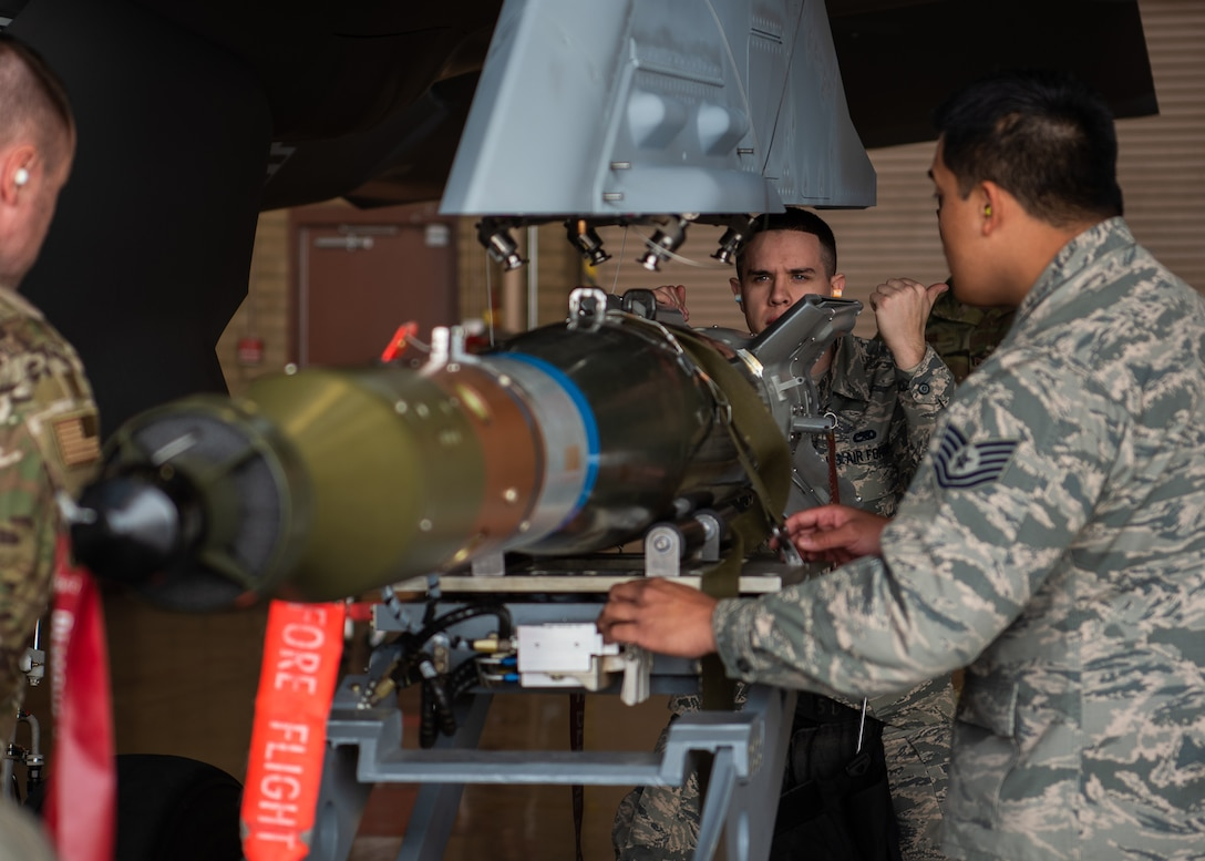 Senior Airman Levi Aydt, 56th Component Maintenance Squadron load crew member, directs the jammer driver to position dummy munitions on an external pylon, Feb. 13, 2019 at Luke Air Force Base, Ariz. The F-35A Lightning II can have external pylons installed for additional munitions while in combat. (U.S. Air Force photo by Airman 1st Class Aspen Reid)