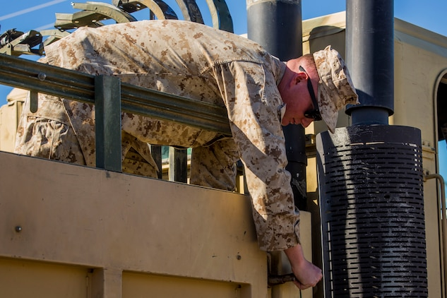 """U.S. Marine Corps Cpl. Tristen Bland, a motor transport operator assigned to 1st Battalion, 5th Marines, Camp Pendleton, Calif., works on a 7-ton Medium Tactical Vehicle Replacement (MTVR) during a stop at Marine Corps Air Station (MCAS) Yuma, Ariz., Jan. 23, 2019.The team of mortar men and motor transport operators stopped at MCAS Yuma to receive mortar rounds in preparations for joint exercise """"Winter Fury."""" Winter Fury provided 3rd Marine Air Wing (MAW) Marines the opportunity to exercise the skills needed as the aviation combat element of the Marine Air Ground Task Force during a combat deployment. (U.S. Marine Corps photo by Cpl. Isaac D. Martinez)"""