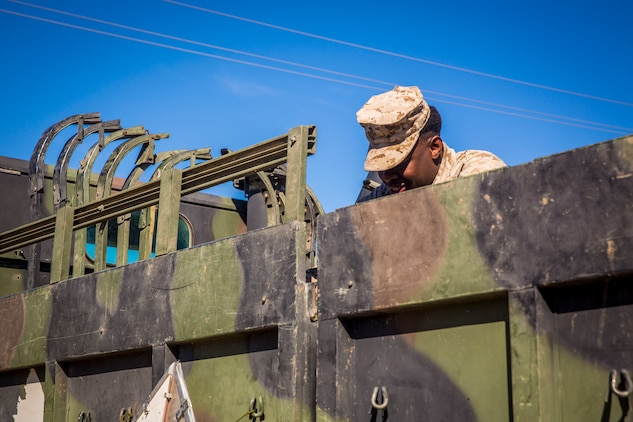 """U.S. Marine Corps Cpl. Giovania Mullins, a motor transport operator assigned to 1st Battalion, 5th Marines, Camp Pendleton, Calif., works on a 7-ton Medium Tactical Vehicle Replacement (MTVR) during a stop at Marine Corps Air Station (MCAS) Yuma, Ariz., Jan. 23, 2019.The team of mortar men and motor transport operators stopped at MCAS Yuma to receive mortar rounds in preparations for joint exercise """"Winter Fury."""" Winter Fury provided 3rd Marine Air Wing (MAW) Marines the opportunity to exercise the skills needed as the aviation combat element of the Marine Air Ground Task Force during a combat deployment. (U.S. Marine Corps photo by Cpl. Isaac D. Martinez)"""