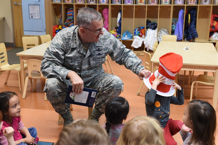 A service member puts a hat on a child.