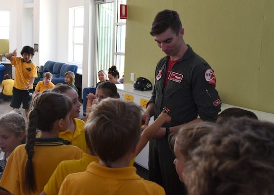 U.S. Air Force 1st Lt. Connor Howard, an F-22 Raptor pilot with the 90th Fighter Squadron, Joint Base Elmendorf-Richardson, Alaska, hands out souvenirs to students from Lara Primary School in Geelong, Victoria, Australia, Feb. 26, 2019.