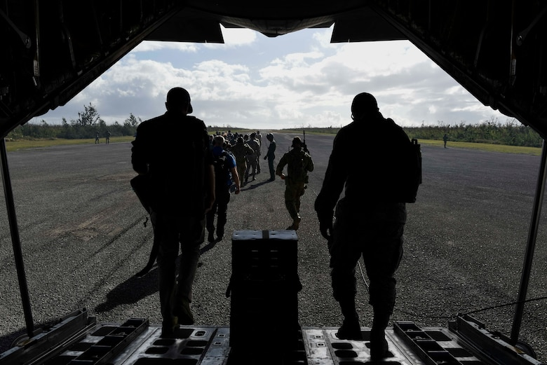 Service members from the United States, Royal Australian Air Force, and the Japan Air Self-Defense Force exit a JASDF C-130H Feb. 27, 2019, at Tinian, Commonwealth of the Northern Marianas. Service members from the U.S., Royal Australian Air Force, and the Japan Air Self-Defense Force exercised their Humanitarian Assistance and Disaster Relief skills together on Tinian by providing emergency medical care and secure transportation for simulated patients. (U.S. Air Force photo by Tech. Sgt. Jake Barreiro)