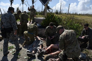 Service members from the United States, Royal Australian Air Force, and Japan Air Self-Defense Force work together to treat simulated injuries on personnel during Cope North 2019, Feb. 27, 2019, at Tinian, Commonwealth of the Northern Marianas.  Service members from the U.S., Royal Australian Air Force, and the Japan Air Self-Defense Force exercised their Humanitarian Assistance and Disaster Relief skills together on Tinian by providing emergency medical care and secure transportation for simulated patients. (U.S. Air Force photo by Tech. Sgt. Jake Barreiro)