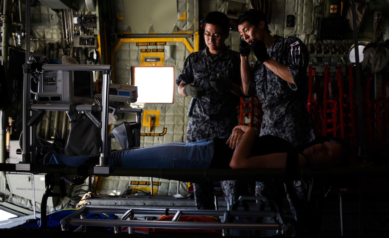 Medical service members from the Japan Air Self-Defense Force perform simulated emergency medical care and transportation on U.S. Airman 1st Class Kelly Destiny, 36 Mobility Response Squadron Air Transportation apprentice, during an exercise scenario for Cope North 2019, Feb. 27, 2019, at Andersen Air Force Base, Guam. On Feb. 27, service members from the U.S., Royal Australian Air Force, and the Japan Air Self-Defense Force exercised their Humanitarian Assistance and Disaster Relief skills together on Tinian by providing emergency medical care and secure transportation for simulated patients. (U.S. Air Force photo by Tech. Sgt. Jake Barreiro)