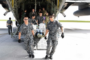 Medical service members from the Japan Air Self-Defense Force perform simulated emergency medical care and transportation on U.S. Airman 1st Class Kelly Destiny, 36 Mobility Response Squadron Air Transportation apprentice, during an exercise scenario for Cope North 2019, Feb. 27, 2019, at Andersen Air Force Base, Guam. Service members from the U.S., Royal Australian Air Force, and the Japan Air Self-Defense Force exercised their Humanitarian Assistance and Disaster Relief skills together on Tinian by providing emergency medical care and secure transportation for simulated patients. (U.S. Air Force photo by Tech. Sgt. Jake Barreiro)