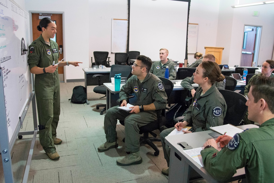 Capt. Christine Durham (left), Pilot Training Next instructor pilot, gives a briefing to her students prior to a training mission at the Armed Forces Reserve Center in Austin, Texas, Feb. 5, 2019. The current PTN class is comprised of 26 students, including 16 active duty officer students (six of whom are participating in a remotely-piloted aircraft only track), two Air National Guard officers, two U.S. Navy officers, one Royal Air Force officer, and five enlisted Airmen. (U.S. Air Force photo by Sean M. Worrell)