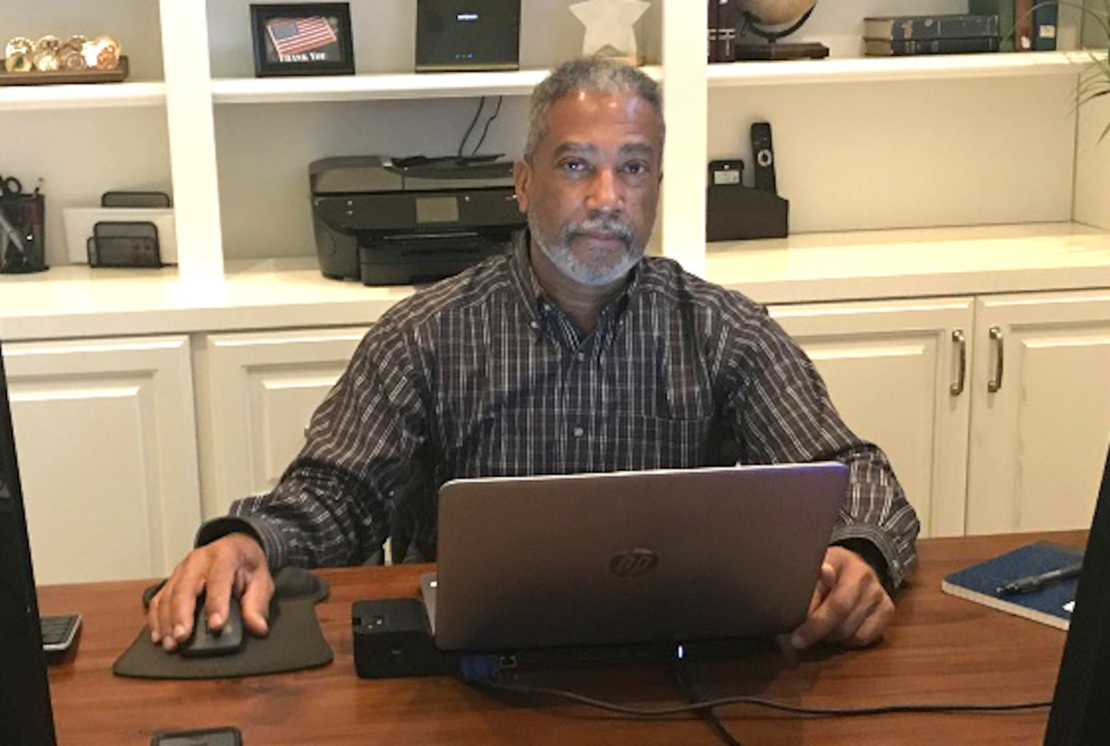 a man sits at a desk in front of computer