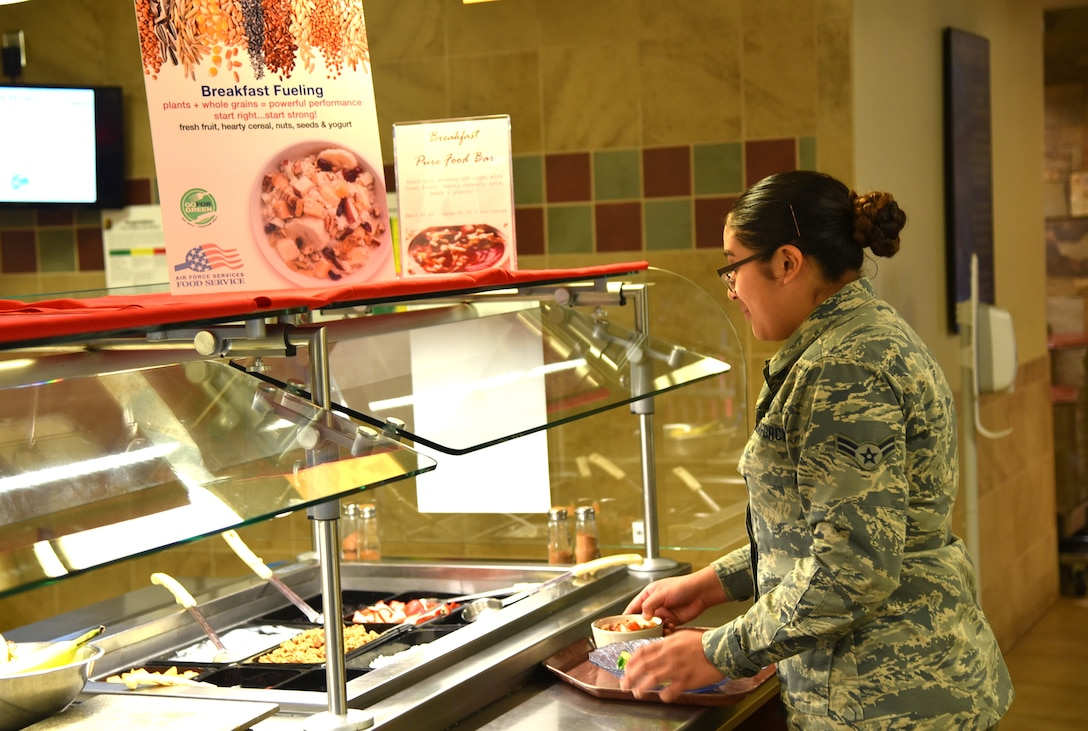 An Airman builds her meal using fresh, health options on the Pure Bar at the Aragon Dining Facility on Peterson AFB, Colorado. Pure Bars, packed with whole grains, fresh fruits and other more nutritional offerings, are part of the Air Force's Go For Green program designed to provide healthy, power fueling for Airmen. (U.S. Air Force photo by Carrie Grover)