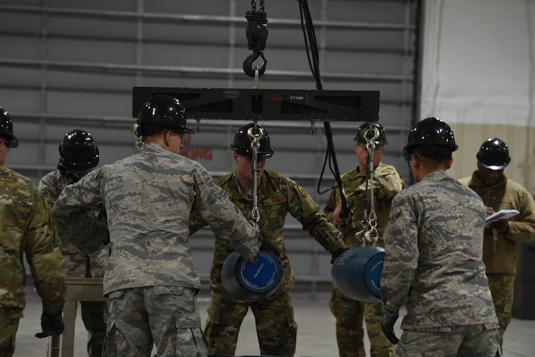 A team of Airmen work together to bring three small-diameter bombs onto a conveyer during the qualifying round of the second annual Air Force Combat Operations Competition on Ellsworth Air Force Base, S.D., Feb. 5, 2019. The competition is Air Force-wide and is used to determine the best of the best in munitions operations. (U.S. Air Force photo by Airman John Ennis)
