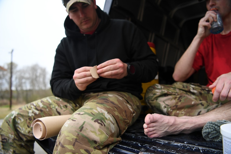 An independent duty medical technician with the 24th Special Operations Wing bandages a Special Tactics Airman's foot during the Special Tactics Memorial March Feb 26, 2019, near Eunice, Louisiana.