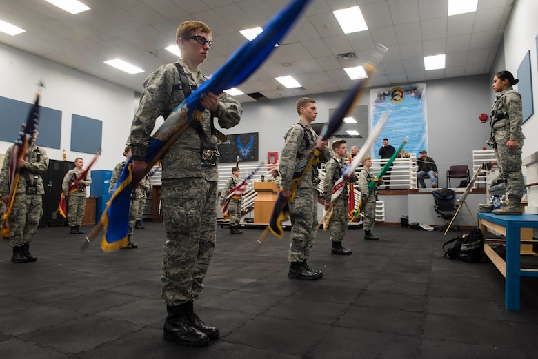 """U.S. Air Force Airman 1st Class Larrah Lara, 92nd Air Refueling Wing base honor guardsman, instructs Civil Air Patrol cadets from the 21st Fairchild Composite Squadron on the movement of """"present colors' at Fairchild Air Force Base, Washington, Feb. 26, 2019.  When """"presenting the colors"""" honor guardsmen keep the U.S. flag upright in the """"port arms"""" position while slowly lowering the rest of the flags. (U.S. Air Force photo by Airman 1st Class Lawrence Sena)"""