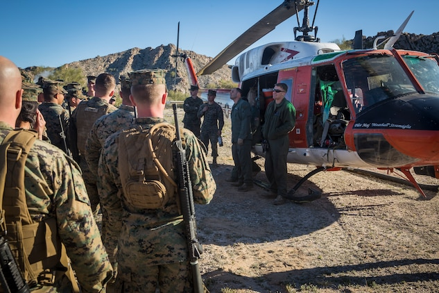 """U.S. Marines and Sailors assigned to Marine Corps Air Station (MCAS) Yuma's Search and Rescue (SAR) unit talk about the SAR unit's mission to non-commisioned officers (NCOs) from MCAS Yuma, Ariz., Feb. 7, 2019 as a part of """"Operation Backbone."""" Operation Backbone is a quarterly unit exercise meant to strengthen the warrior's spirit in the non-commisioned officers (NCOs) and promote cohesion between them. The exercise consisted of a hike with the Headquarters and Headquarters Squadron (H&HS)  commanding officer and acting sergeant major, several classes, and a warriors night. Classes included simulated room clearing training, terrain model training, improvised explosive devices (IED) training, and the Family Advocacy Program on station sent out a representative to talk to the NCOs about leadership. (U.S. Marine Corps photo by Cpl. Isaac D. Martinez)"""