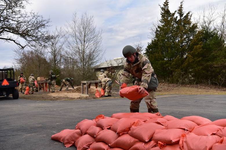 Airmen adds sandbag to pile