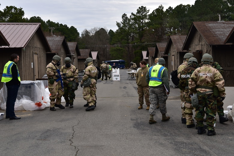 Airmen stand around in chemical protection gear