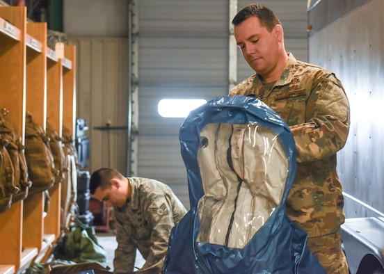Master Sgt. Kevin McGinnis, 14th Civil Engineer Squadron Readiness and Emergency Management Flight superintendent, and Senior Airman Brett Jones, 14th CES Readiness and Emergency Management Flight journeyman, show how to properly put on hazardous material gear Feb. 26, 2019, on Columbus Air Force Base, Mississippi. McGinnis and his team responsible for the base's emergency planning during natural disasters, chemical, biological, radioactive or nuclear attacks, certain aircraft mishaps, and other incidents. (U.S. Air Force photo by Senior Airman Beaux Hebert