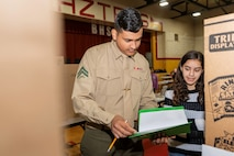 Lance Cpl. Jose Corpus, ammunition technician specialist, reviews the grading rubric while discussing a project with a student at the STEAM Fair aboard Barstow High School, Barstow, Calif., Feb. 21. (U.S. Marine Corps Photo by Jack J. Adamyk)