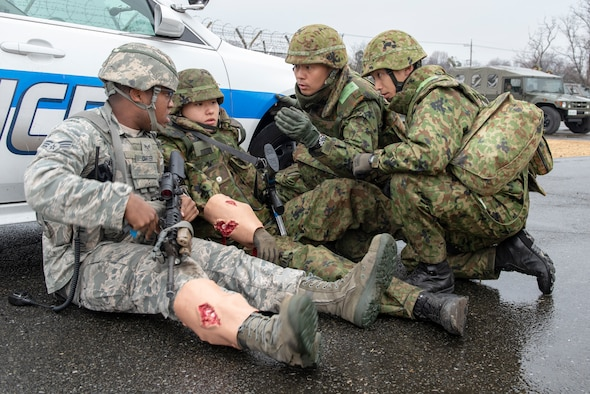 Senior Airman Clifton Carter, 374th Security Forces Squadron patrolman, and members of the Japan Ground Self-Defense Force (JGSDF) from the 34th Infantry Regiment out of Camp Itazuma in Gotemba, Japan discuss a plan of attack during the sniper fire portion of Guard and Protect 2019 at Yokota Air Base, Japan, Feb. 28, 2019.