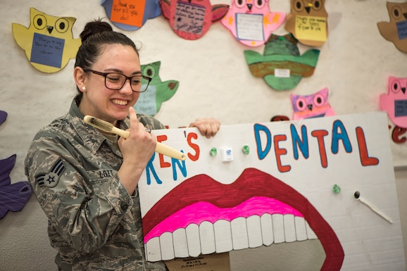 U.S. Air Force Senior Airman Courtney Lott, a 35th Dental Squadron dental technician, points to her teeth during a National Dental Health Month workshop at Misawa Air Base, Japan, Feb. 26, 2019. This event provided models for children to apply the techniques shared about proper oral hygiene. (U.S. Air Force photo by Airman 1st Class Collette Brooks)