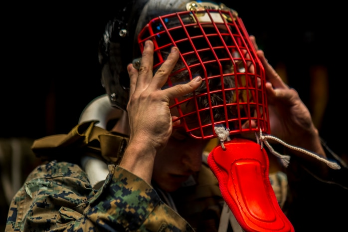 U.S. Marine Cpl. Isaiah Chavez, a heavy equipment mechanic with Combat Logistics Battalion 13, 13th Marine Expeditionary Unit, removes a helmet during the culminating event of a Marine Corps Martial Arts Program instructor course, aboard the Wasp-class amphibious assault ship USS Essex, Dec. 27, 2018. The Essex is the flagship for the Essex Amphibious Ready Group and, with the embarked 13th MEU, is deployed to the U.S. 5th Fleet area of operations in support of naval operations to ensure maritime stability and security in the Central Region, connecting the Mediterranean and the Pacific through the western Indian Ocean and three strategic choke points.