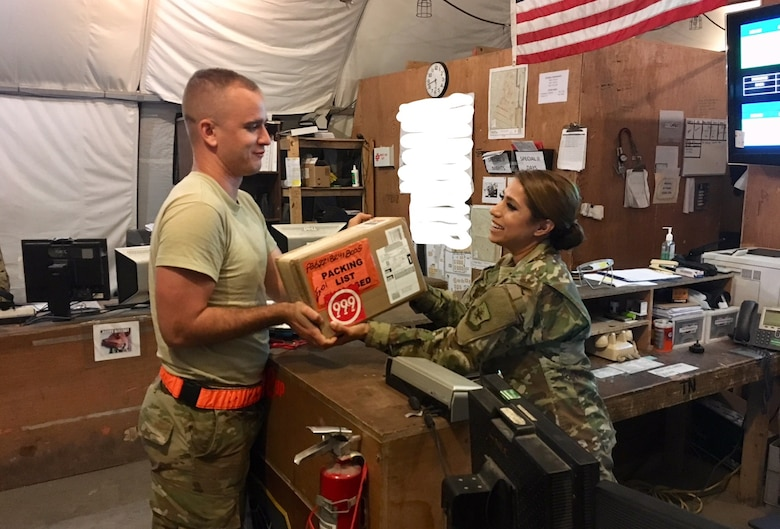 Tech. Sgt. Janet Lindsay, Special Cargo Handler, 8th Expeditionary Air Mobility Squadron, receives a package at Al Udeid Air Base in Qatar.
