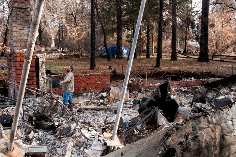 Eric Gowins marvels at the sight of his still-standing fireplace within his decimated home in Paradise, California, Dec. 17, 2018. The Gowins searched for hours to find one possession that means the most to them—Mary's engagement ring. Unfortunately, after sifting through pounds of rubble, they failed. (U.S. Air Force photo by Staff Sgt. Taylor Workman)