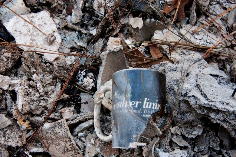 "A broken mug nestled amongst the remains of the Gowins' family home reads: ""Look for the silver lining in that cloud. It's there."" The mug was found while sifting through the wreckage in Paradise, California, Dec. 17, 2018. (U.S. Air Force photo by Staff Sgt. Taylor Workman)"