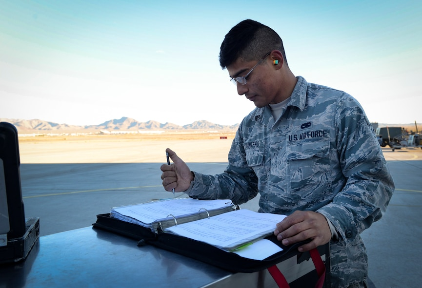 An Airman signs paperwork in a binder on the flight line.