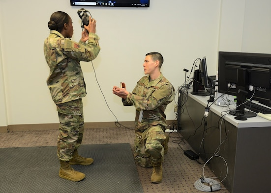 On one knee, Tech. Sgt. Jeremy Neilson, 412th Aircraft Maintenance Squadron, proposes to Staff Sgt. Nori Sannoh following a presentation to base leadership on using virtual reality programs to train F-35 maintenance personnel Dec. 20, 2018. (U.S. Air Force photo by Kenji Thuloweit)