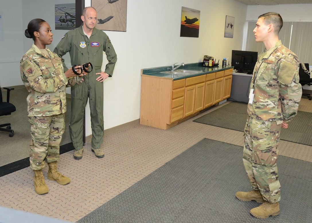 Tech. Sgt. Jeremy Neilson, 412th Aircraft Maintenance Squadron (right), and Staff Sgt. Nori Sannoh, 432nd Maintenance Group, Nellis Air Force Base, Nevada, discuss using virtual reality programs for training with Brig. Gen. E. John Teichert, 412th Test Wing commander, Dec. 20, 2018. (U.S. Air Force photo by Kenji Thuloweit)