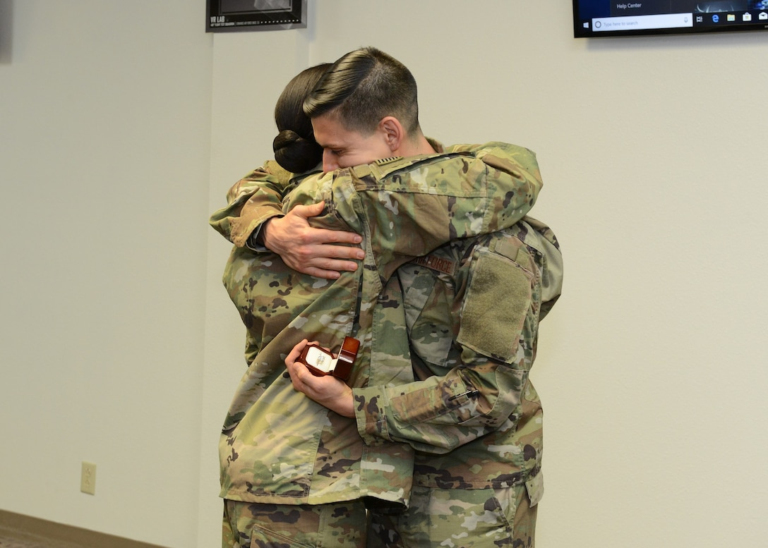Tech. Sgt. Jeremy Neilson, 412th Aircraft Maintenance Squadron, hugs Staff Sgt. Nori Sannoh, 432nd Maintenance Group, Nellis Air Force Base, Nevada, after he surprised her with a marriage proposal Dec. 20, 2018. (U.S. Air Force photo by Kenji Thuloweit)